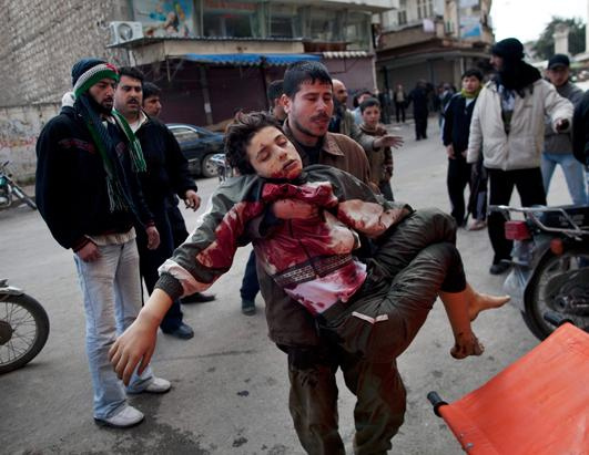 A Syrian man carries a wounded boy.
