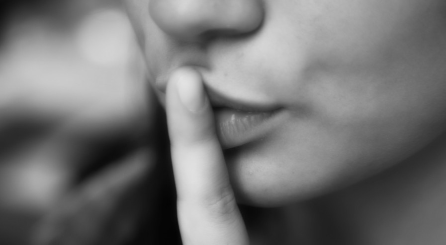 Mouth of girl who asks for silence with gesture
